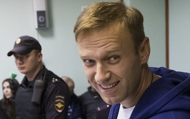 Russian opposition leader Alexei Navalny smiles as he speaks to the media during a break in the hearing on his appeal in a court in Moscow, Russia, Friday, Oct. 6, 2017. The Moscow City Court on Friday upheld a 20-day jail term for Navalny for calling for an unsanctioned protest. (AP Photo/Pavel Golovkin)