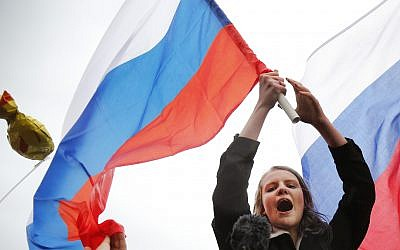 Demonstrators shout slogans and wave Russian flags during a rally in Moscow, Russia October 7, 2017. (AP Photo/Alexander Zemlianichenko)