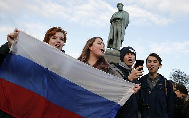 Demonstrators sing as they hold the Russian flag during a rally in Moscow, Russia, Saturday, Oct. 7, 2017. Opposition leader Alexei Navalny has worked to organize protests in support of his presidential bid across Russia on Saturday, President Vladimir Putin's birthday. (AP Photo/Alexander Zemlianichenko)