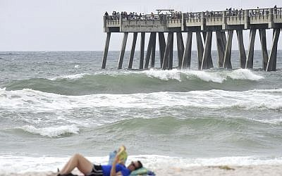 A beachgoer relaxes on the beach on Saturday October 7, 2017, as Hurricane Nate pushes waves from the Gulf of Mexico against the fishing pier in Navarre Beach, Florida (Nick Tomecek/Northwest Florida Daily News via AP)