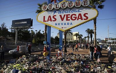 Flowers, candles and other items surround the famous Las Vegas sign at a makeshift memorial for victims of a mass shooting in Las Vegas, October 9, 2017. (AP/John Locher)