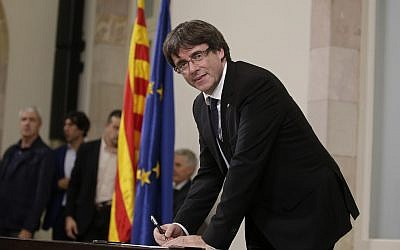 Catalan regional President Carles Puigdemont signs an independence declaration document after a parliamentary session in Barcelona, Spain, Tuesday, Oct. 10, 2017. (AP Photo/Manu Fernandez)