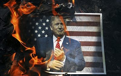 In this Wednesday, Sept. 27, 2017 file photo, a portrait of US President Donald Trump is set on fire by Iranian mourners during the state funeral of Mohsen Hojaji, a young Revolutionary Guard soldier beheaded by the Islamic State group in Syria, in Tehran, Iran. (AP/Ebrahim Noroozi)