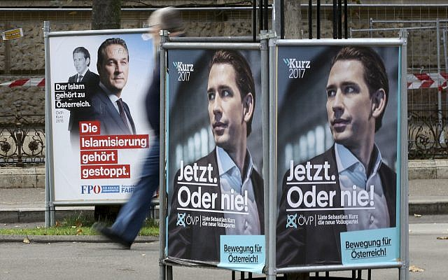 In this photo taken Wednesday, Oct. 11, 2017, a person passes posters of the right-wing Freedom party, FPOE, and the conservative Austrian People's Party, OEVP, from left, in Vienna, Austria, Wednesday, Oct.11, 2017. (AP Photo/Ronald Zak)