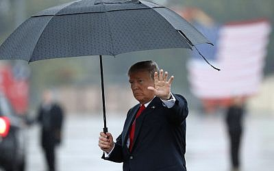 US President Donald Trump waves as he carries an umbrella walking on the tarmac to his limousine at Harrisburg International Airport, Wednesday October 11, 2017, in Middletown, Pennsylvania (AP Photo/Alex Brandon)