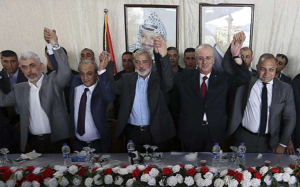From left in front row, Hamas leader in the Gaza Strip Yahya Sinwar, Head of Palestinian General Intelligence Majid Faraj, Head of the Hamas political bureau Ismail Haniyeh, PA Prime Minister Rami Hamdallah and an Egyptian mediator hold their hands up during a meeting in Gaza City, October 2, 2017. (AP Photo/Prime Minister Office, File)
