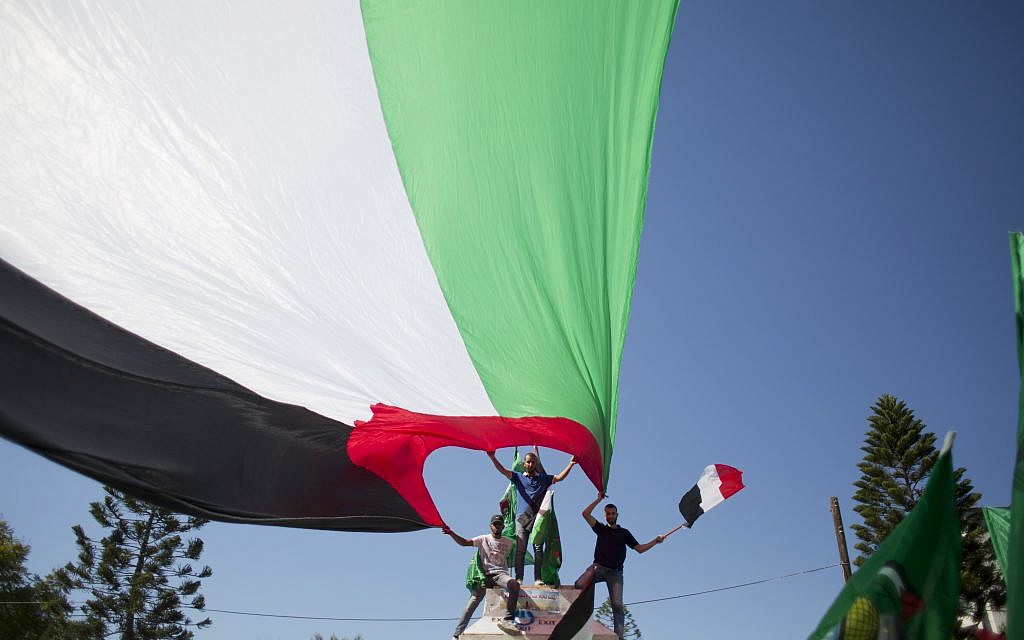 Palestinians in Gaza City wave Palestinian and Egyptian flags to celebrate the reconciliation agreement between Hamas and Fatah in Egypt, October 12, 2017. (AP Photo/Khalil Hamra)