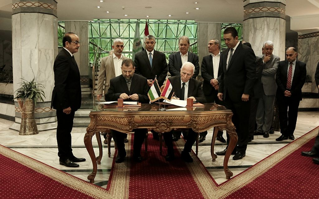 Senior Fatah official Azzam al-Ahmad, center right, and Hamas' representative, Saleh al-Arouri, center left, sign a reconciliation deal during a short ceremony at the Egyptian intelligence complex in Cairo, Egypt, Thursday, Oct. 12, 2017. Thursday's signing came after two days of negotiations in the Egyptian capital on the governing of the Gaza Strip as part of the most serious effort to date to end the 10 year rift between the rival Palestinian groups. (AP Photo/Nariman El-Mofty)