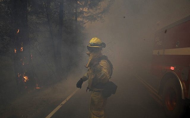 A firefighter gestures to his colleagues as he walks through thick smoke from a wildfire Thursday, Oct. 12, 2017, near Calistoga, Calif.  (AP Photo/Jae C. Hong)