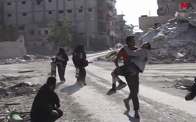 This frame grab from a video provided on Friday, Oct. 13, 2017 by Turkey-based Kurdish Mezopotamya agency media outlet  shows Syrian civilians run on a damaged street as they fleeing from the areas that still controlled by the Islamic State militants, in Raqqa, Syria. Scores of civilians including women and children are fleeing the last few remaining neighborhoods held by the Islamic State group in Syria's northern city of Raqqa, ahead of an anticipated final push by US-backed fighters seeking to liberate the city. (Mezopotamya Agency, via AP)