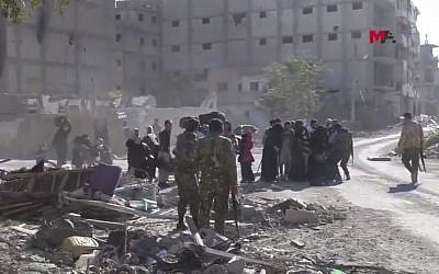 This frame grab from a video provided on Friday, Oct. 13, 2017 by Turkey-based Kurdish Mezopotamya agency media outlet that is consistent with independent AP reporting, shows US-backed Syrian Democratic Forces (SDF) fighters, stand around Syrian civilians who fled from the areas that still controlled by the Islamic State militants, in Raqqa, Syria. (Mezopotamya Agency, via AP)