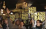 Demonstrators hold posters 'Nazis get off' during a demonstration against the Austrian Freedom Party FPOe in Vienna, Austria, Friday, Oct. 13, 2017. (AP Photo/Ronald Zak)