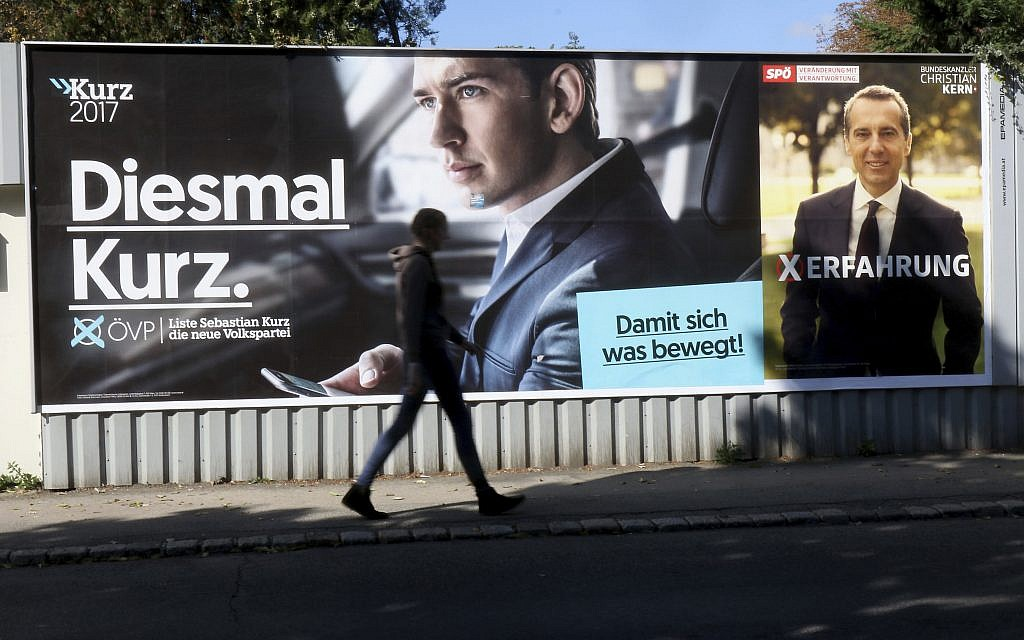 A person passes posters of the conservative Austrian People's Party, OEVP, left,  and the Austrian Social Democrats, SPOE, in Vienna, Austria, October 14, 2017. (AP Photo/Ronald Zak)