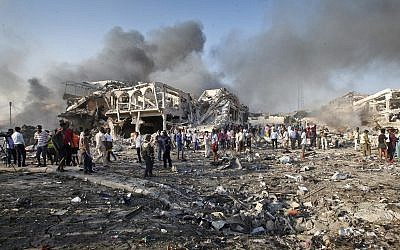 Somalis gather and search for survivors by destroyed buildings at the scene of a blast in the capital Mogadishu, Somalia, October 14, 2017. (AP Photo/Farah Abdi Warsameh)