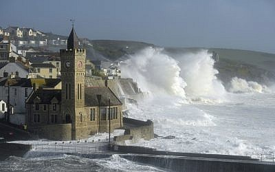 Waves break around the church in the harbor at Porthleven, Cornwall southwestern England, as the remnants of  Hurricane Ophelia begins to hit parts of Britain and Ireland. (Ben Birchall/PA via AP)