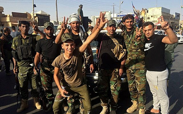 Iraqi security forces and volunteers celebrate in front of Governorate Council Building in Kirkuk, Iraq, October 16, 2017. (AP/Emad Matti)