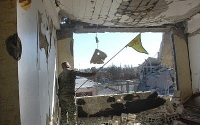 In this picture taken on Monday Oct. 16, 2017 and provided by The Syrian Democratic Forces (SDF), a U.S.-backed Syrian Kurdish forces outlet that is consistent with independent AP reporting, shows a Syrian Democratic Forces (SDF) fighter, waves his Kurdish party flag at the front line where they battle against the Islamic State militants, in Raqqa, Syria. The U.S-backed Syrian forces battling the Islamic State group in Syria say Raqqa's national hospital, one of the militants' last holdouts in city has been captured.(Syrian Democratic Forces via AP)