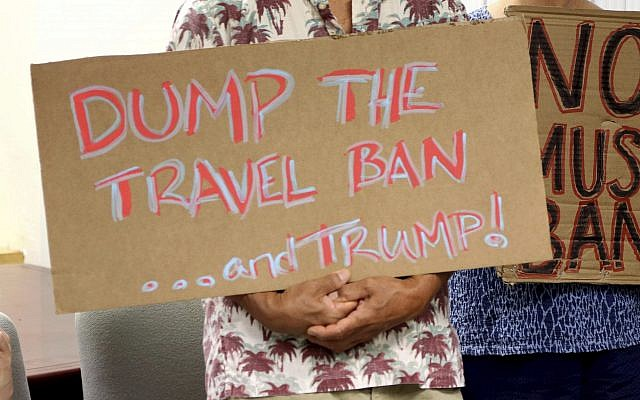 In this file photo from June 30, 2017, critics of US President Donald Trump's travel ban hold signs during a news conference in Honolulu. (AP Photo/Caleb Jones, File)