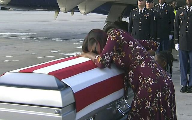 In this Tuesday, October 17, 2017, frame from video, Myeshia Johnson cries over the casket of her husband, Sgt. La David Johnson, who was killed in an ambush in Niger, upon his body's arrival in Miami. (WPLG via AP)