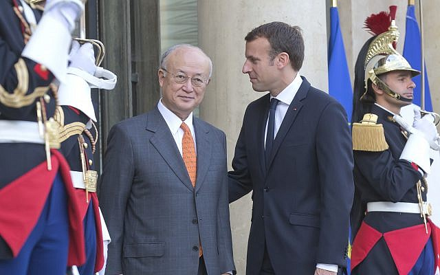 French President Emmanuel Macron, left, welcomes Director General of the International Atomic Energy Agency, IAEA, Yukiya Amano for a meeting at the Elysee Palace in Paris, France, October 19, 2017. (AP Photo/Michel Euler)