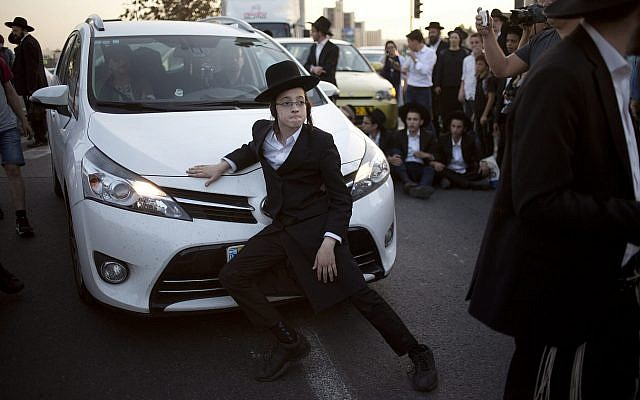 An ultra-Orthodox Jew blocks a car from crossing a main junction during a demonstration in Jerusalem against the conscription of members of the ultra-Orthodox community to the IDF on October 19, 2017. (AP Photo/Ariel Schalit)