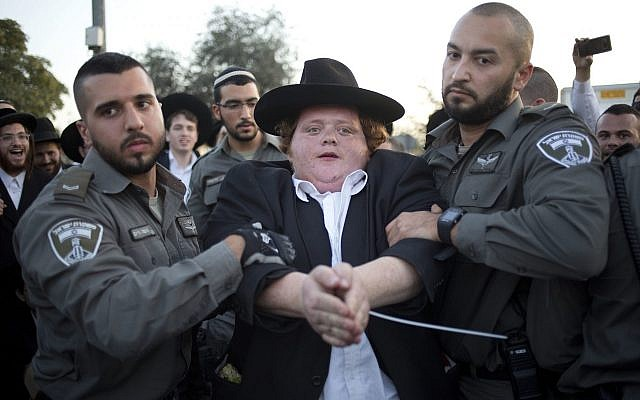 Police officers arrests an ultra-Orthodox Jew during a demonstration in Jerusalem against the conscription of members of the ultra-Orthodox community to the IDF on October 19, 2017. (AP Photo/Ariel Schalit)