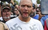 Blood runs from the lip of a man wearing a shirt with swastikas after he was punched by a protester outside a University of Florida auditorium where white nationalist Richard Spencer was preparing to speak, Thursday, October 19, 2017 in Gainesville, Fla. (Will Vragovic/Tampa Bay Times via AP)