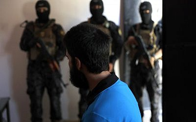 In this file picture taken on Friday, July 21, 2017, Kurdish soldiers from the Anti-Terrorism Units, background, stand in front a blindfolded Turkish suspected Islamic State member, Onur, at a security center, in Kobani, Syria. (AP Photo/Hussein Malla)