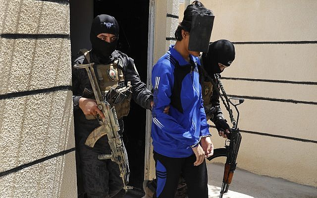 In this file picture taken on Friday, July 21, 2017, Kurdish soldiers from the Anti-Terrorism Units, carry a blindfolded an Indonesian man suspected of Islamic State membership, at a security center, in Kobani, Syria. (AP Photo/Hussein Malla, File)