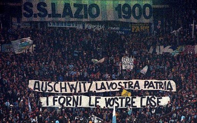 "In this Nov. 29, 1998 file photo, Lazio fans display banners from the stands reading ""Auschwitz is Your Homeland. The Ovens are Your Homes"" during a Serie A match between Lazio and AS Roma, at Rome's Olympic stadium. Lazio fans have a long history of racism and anti-Semitism but the Roman club's supporters established a new low on Sunday, Oct. 22,  2017 when they littered the Stadio Olimpico with superimposed images of Anne Frank _ the young diarist who died in the Holocaust _ wearing a Roma jersey.  (AP Photo/Plinio Lepri,)"