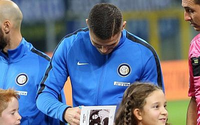 Inter's captain Mauro Icardi signs  Anne Frank's diary for a child, prior to the Italian Serie A soccer match between Inter and Sampdoria at the San Siro stadium in Milan, Italy, October 24, 2017. (Matteo Bazzi/ANSA via AP)
