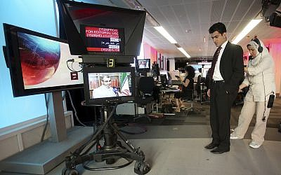 In this Friday June 26, 2009 photo, BBC Persian service presenter Fardad Farahzad, right, gets ready to present the news, at the corporation's London headquarters. (AP Photo/Simon Dawson, File)