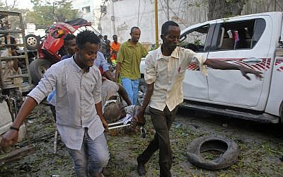 Somalis carry away the wounded civilian who was injured in a car bomb that was detonated in Mogadishu, Somalia Saturday, October 28, 2017.  (AP Photo/Farah Abdi Warsameh)