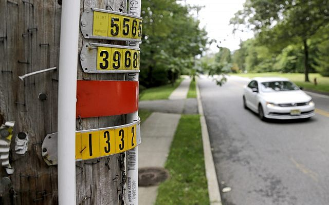 In this Aug. 5, 2017, file photo, a vehicle drives past polyvinyl chloride piping attached to a utility pole, signifying an outdoor area known as an eruv where Jewish residents observing certain restrictions during the Sabbath are permitted to carry items from home, along Airmount Road in Mahwah, N.J.  (AP Photo/Julio Cortez, File)
