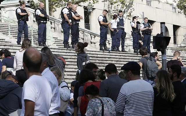 Passengers wait in front a line a police officers blocking the access to Marseille's main train station Sunday, Oct. 1, 2017 in Marseille, southern France. French police have warned people to avoid Marseille's main train station following a knife attack in which two people and the attacker were killed. (AP Photo/Claude Paris)