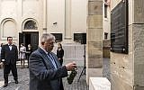 Director of the Holocaust Memorial Center Szabolcs Szita lays a wreath at a memorial plaque dedicated to the late director of the one-time Antiqua Printing House Emil Wiesmeyer who helped to save the lives of thousands of Jewish Hungarians during WWII, October 18, 2017. (Zsolt Szigetvary/MTI via AP)