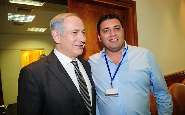 Israeli Prime Minister Benjamin Netanyahu and Spotoption founder Pini Peter pose together at a charity event in the Prime Minister's Office in October 2011 (Berele Sheiner)