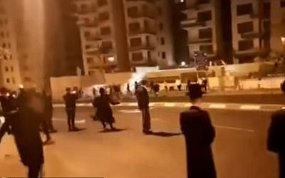 Screen capture from video showing supporters of the Beitar Jerusalem soccer club and ultra-Orthodox protesters throwing stones at each in Jerusalem, October 29, 2017. (YouTube/Hadashot Kol HaOlam Kulo)