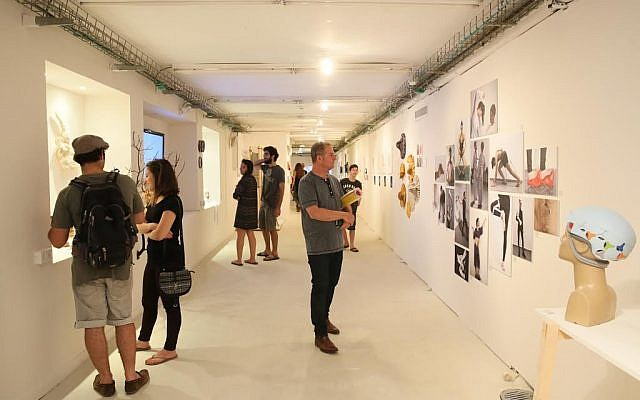 People viewing artwork at the Bezalel Academy of Art and Design's annual student exhibition in Jerusalem, July 2016. (Courtesy of Bezalel via JTA)