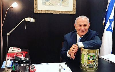 Prime Minister Benjamin Netanyahu poses with a large can of pickles on October 23, 2017. (Courtesy: Prime Minister's Office)