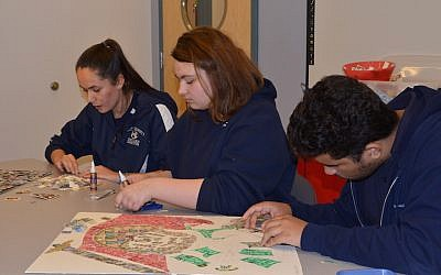 "Foxborough Regional Charter School High school students selecting stamps to use on two HSP stamps collages, ""I Am the Last Witness"" and ""Books Cannot Be Killed by Fire."" (Courtesy of Charlotte Sheer/Holocaust Stamp Project)"
