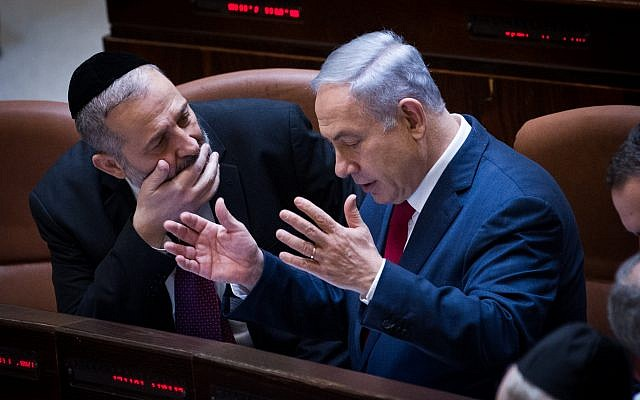 File: Prime Minister Benjamin Netanyahu, right, speaks with Interior Minister Aryeh Deri during a plenum session in the Knesset, January 11, 2016. (Miriam Alster/Flash90)