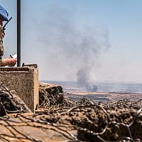 Illustrative photo of a UN observer at a lookout point as smoke rising at a Syrian village near the Israeli-Syrian border in the Golan Heights during fights between the rebels and the Syrian army, June 25, 2017. (Basel Awidat/Flash90)