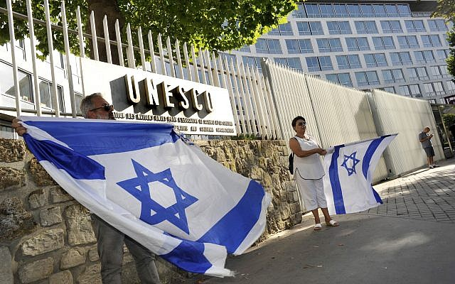 French Jews hold Israeli flags as they take part at a demonstration against UNESCO, near the cultural agency's Paris headquarter, July 17, 2017. (Serge Attal/Flash90)