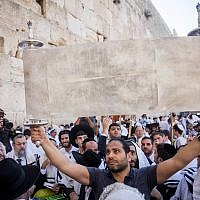 Illustrative: Jewish worshipers hold up the Torah scroll at the annual priestly blessing during the Sukkot holiday at the Western Wall in the Old City of Jerusalem on October 8, 2017. (Yonatan Sindel/Flash90)