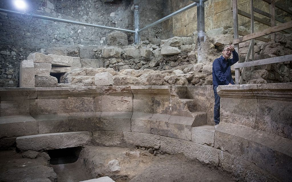 Joe Uziel, an archaeologist from the Israel Antiquity Authority, cleans stones at the site of an ancient Roman theater-like structure, hidden for 1,700 years, adjacent to the Western Wall underneath Jerusalem's Old City on October 16, 2017 (Yonatan Sindel/Flash90)