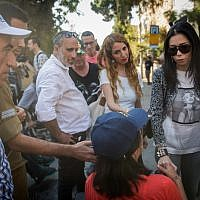Businesswoman Nicol Raidman, right, speaks with disabled rights protester Hannah Akiva, center, and other activists at the entrance to the Prime Minister's Residence, Jerusalem, October 17, 2017. (Yonatan Sindel/Flash90)