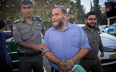 Lehava chairman Benzi Gopstein is brought to the Jerusalem Magistrate's Court, October 22, 2017 (Yonatan Sindel/Flash90)