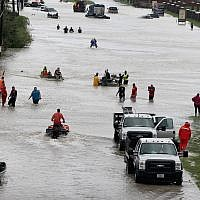 Houston residents making their way out of a flooded neighborhood after it was inundated with rainwater following Hurricane Harvey, Aug. 29, 2017. (Scott Olson/Getty Images via JTA)