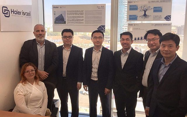 Galit Jacobovitz (sitting down, left) with Daniel Oleiski, left, standing, and with Wang Ye, third from left and the rest of the Haier delegation during their visit to Israel. Oct. 24, 2017. (Courtesy)